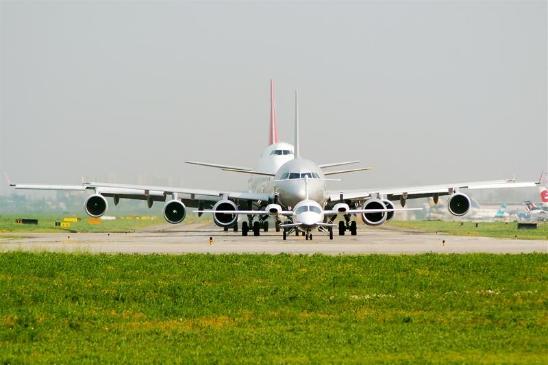 Foto di aerei di diverse dimensioni in fila per il decollo